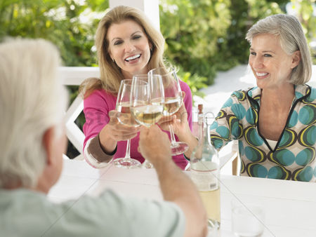 Toasting : Three people toasting with wine glasses sitting at verandah table