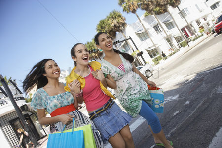 Spending money : Three teenage girls  16-17  carrying shopping bags crossing street