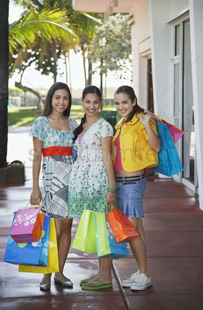 Ponytail : Three teenage girls  16-17  carrying shopping bags standing on street portrait