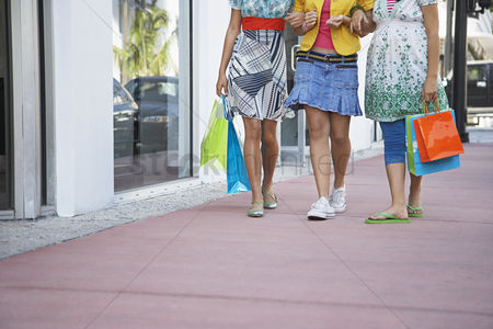 Spending money : Three teenage girls  16-17  carrying shopping bags walking on street low section