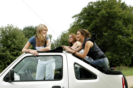 Car : Three women posing on a car