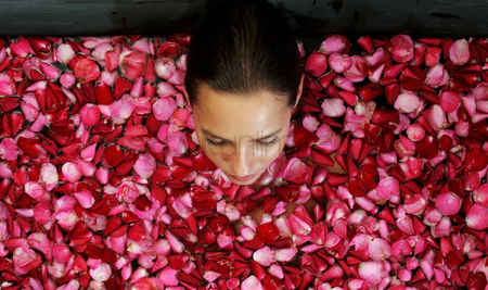 Satisfying : Top view of a woman bathing in a bathtub of flower petals