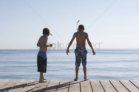 Diving : Two boys  7-11  on jetty wearing snorkelling masks back view