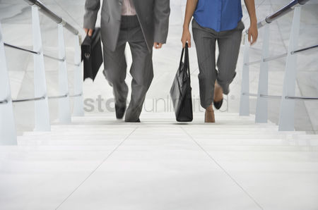 Business suit : Two business people walking up stairs