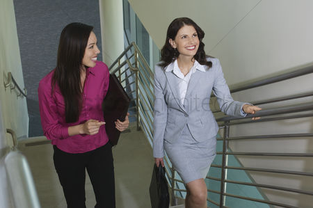 Staircase : Two business women walking up staircase in office building elevated view