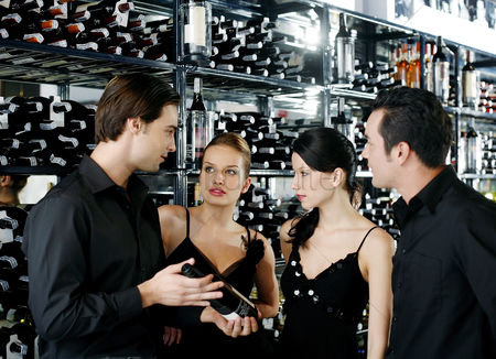 Advice : Two couples choosing wine in the wine cellar