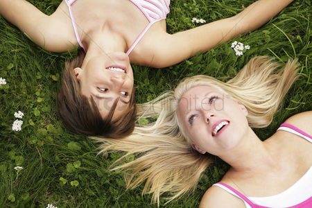 Friends : Two girls lying on the grass