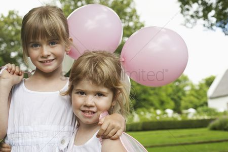 Fashion : Two girls with party balloons in garden