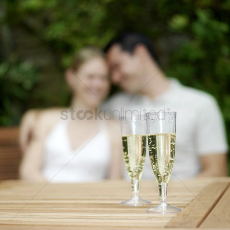 Celebrating : Two glasses of champagne with couple sitting in the background