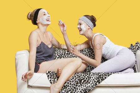 Three quarter length : Two happy young women applying face pack while sitting on sofa over yellow background