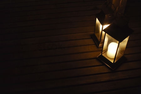 Black background : Two illuminated lanterns on deck at night