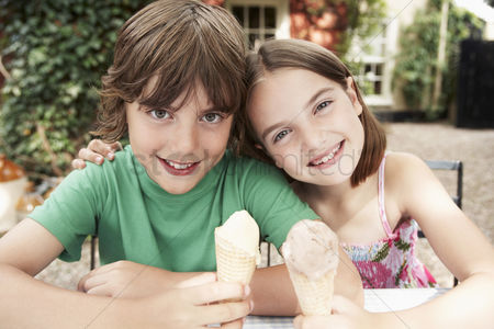 Posing : Two kids eating ice cream cones at table in back yard portrait