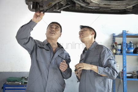 Fixing : Two mechanics looking at underside of a car