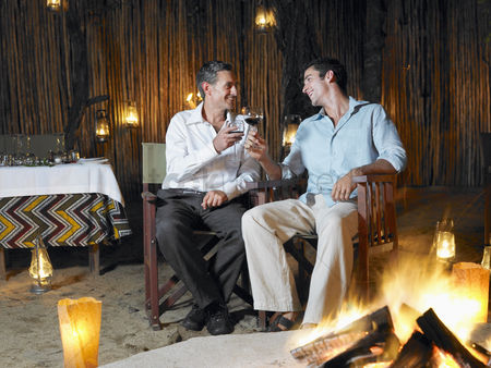 Toasting : Two men sitting by bonfire at outdoor nightclub toasting