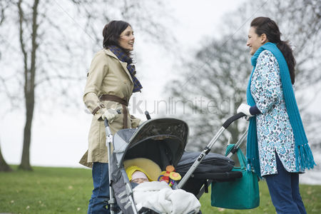 Women group outside : Two mothers in park with babies in strollers