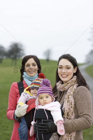 Women group outside : Two mothers with babies in baby carriers in park