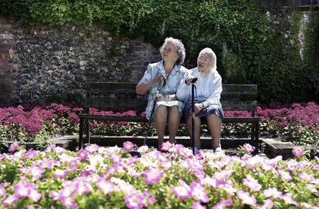 Strong : Two old women sitting on a bench in the garden