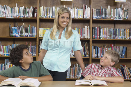 Pupil : Two school boys with teacher in library