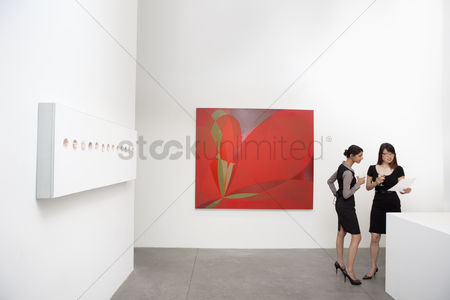 Interior background : Two woman standing next to wall paintings