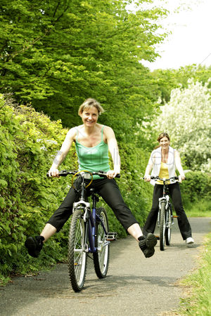 Enjoying : Two women cycling in the park