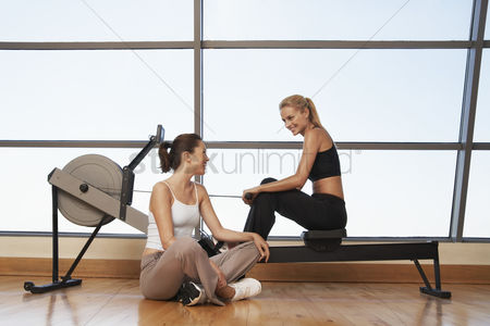 Club : Two women talking at rowing machine in health club