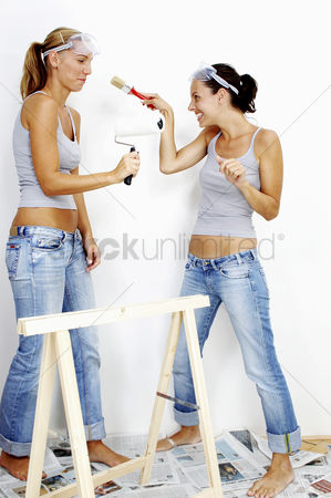 Having fun : Two women with goggles with one holding a roller while the other holding a brush