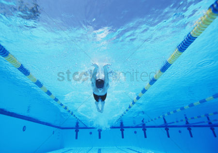 Swimmer : Underwater shot of young male athlete swimming in pool