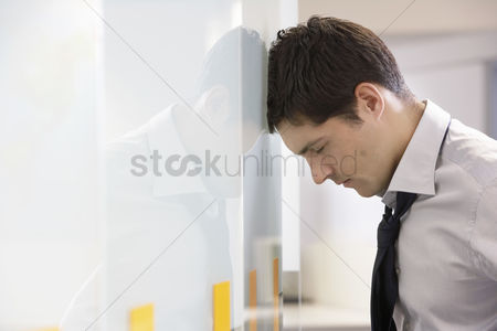 One man only : Unhappy businessman resting head against office wall side view