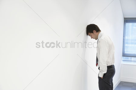 Loss : Unhappy businessman standing with head against wall in empty office