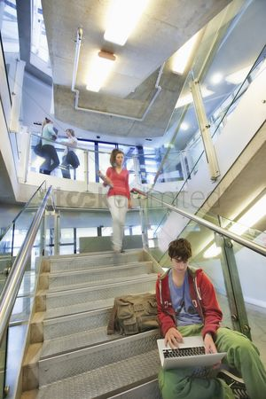 Steps : University student using computer on staircase
