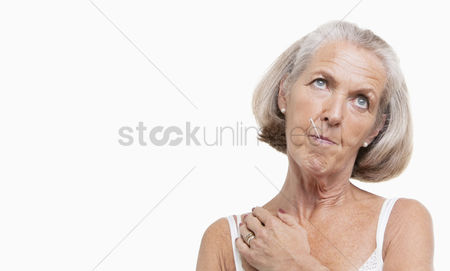 Thermometer : Unwell senior woman with thermometer in mouth against white background