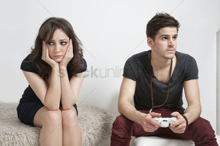 Remote : Upset young woman with young man playing video game