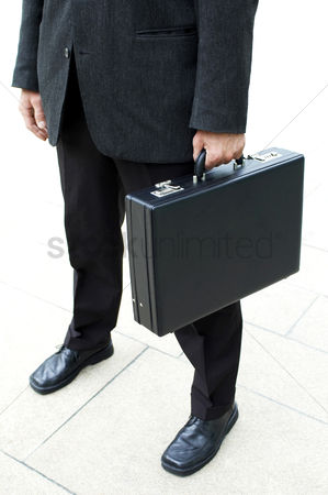 Man suit fashion : Waist down shot of a businessman carrying a briefcase