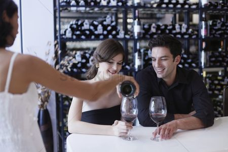 Indulgence : Waitress pouring wine for man and woman at the bar