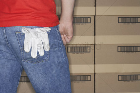 Pocket : Warehouse worker standing in front of stacks of boxes gloves hanging out of back pocket mid section back view