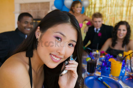 Dance : Well-dressed teenager girl using cell phone at school dance