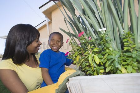 Offspring : Woman and son tending plants