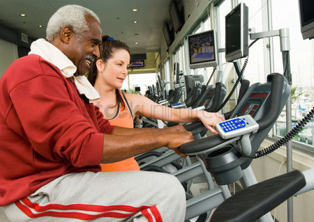 Club : Woman assisting man on exercise bike in gymnasium