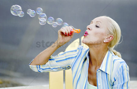 Mature : Woman blowing soap bubbles