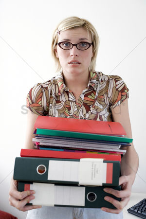 Frowning : Woman carrying files in a home office