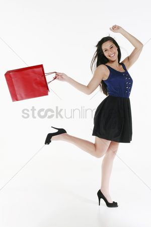Shopping background : Woman carrying shopping bag and skipping happily