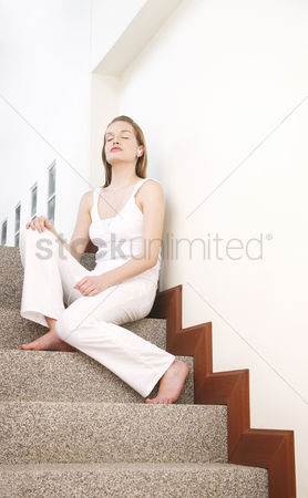 Stairs : Woman closing her eyes while listening to music on a portable mp3 player