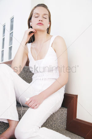 Stairs : Woman closing her eyes while listening to music on the mp3 player