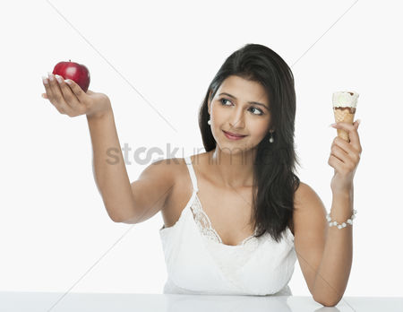 Choosing : Woman comparing an ice cream cone with an apple