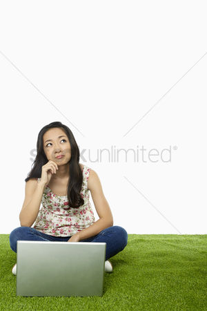 Daydream : Woman contemplating while using laptop