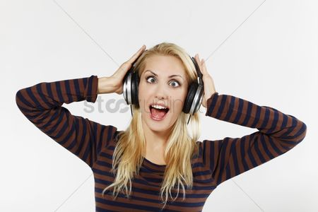 Eastern european ethnicity : Woman crossing eyes while listening to music on the headphones