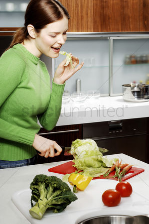 Careful : Woman cutting vegetables in the kitchen