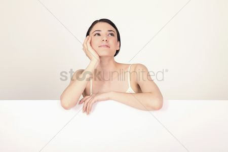 Cardboard cutout : Woman day dreaming on blank placard with hand on chin