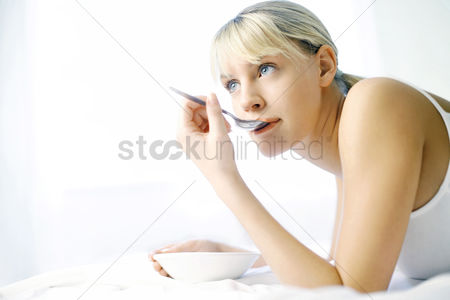 Comfort : Woman daydreaming while eating on the bed