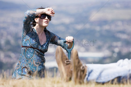 Grass background : Woman digging hole with a dead body beside her